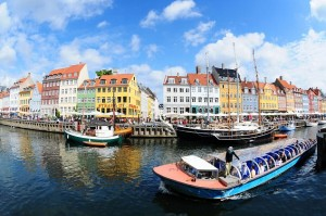 Fisheye view on colorful houses and tour boat in famous canal Nyhavn in Copenhagen, Denmark
